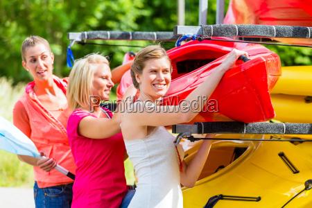 three women unloading kayak from boat