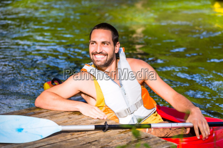 man driving with kayak on forest