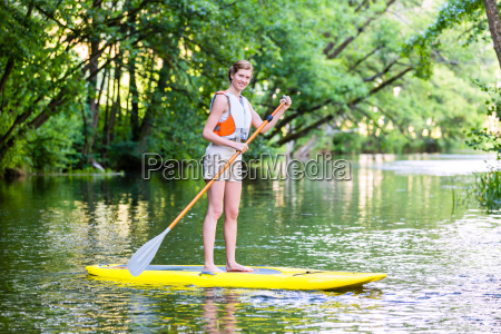 woman paddling with surfboard sup on