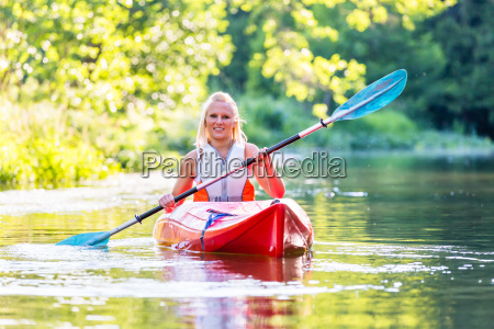 woman driving with kayak on forest