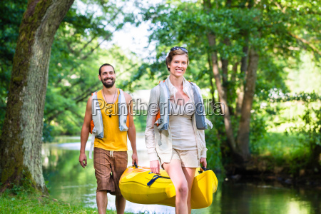 man and woman carrying canoe to