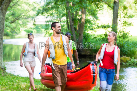 friends carrying kayak or canoe to