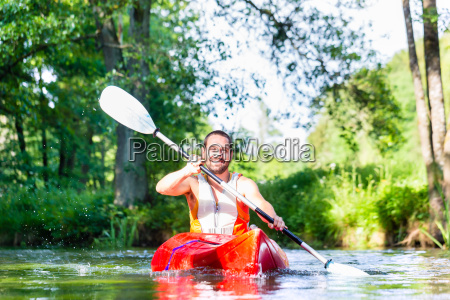 man paddling with canoe on forest