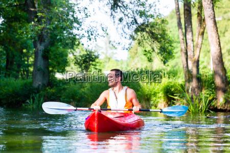 man paddling with canoe or kayak