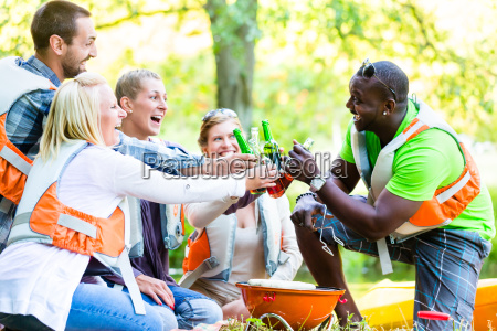 friends barbecue after sports in forest