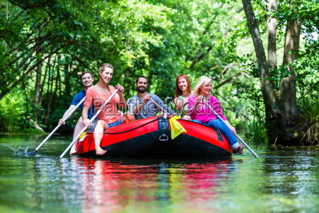 friends paddling on rubber boat at