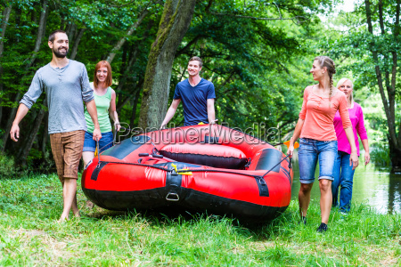 friends carrying rubber boat to forest