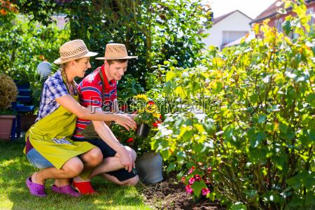 couple in garden planting flowers