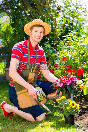man in garden planting flowers