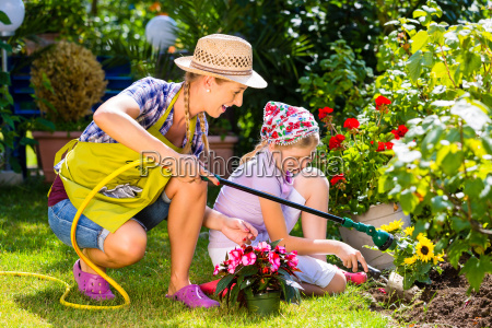 mother and child watering flowers in