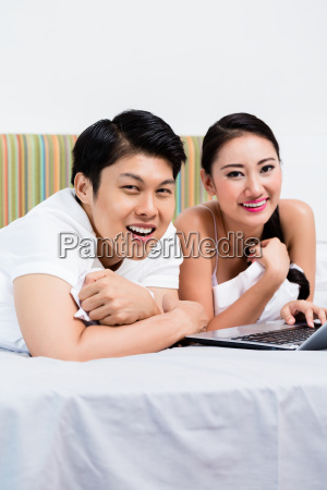 asian couple in bedroom surfing the