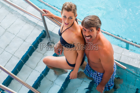 couple on steps of pool in