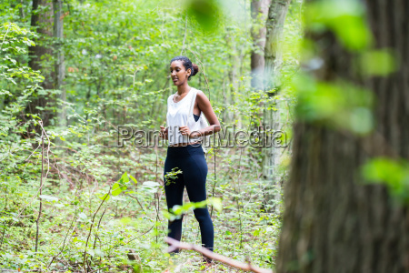 african young woman hiking on forest