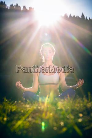 frau macht yoga im sonnenuntergang