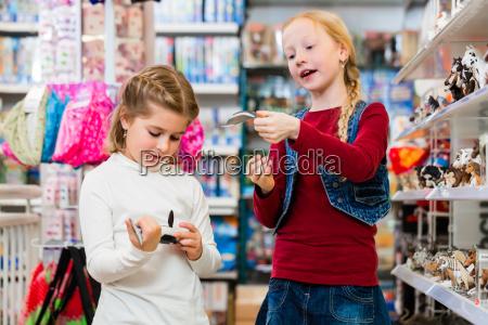 zwei kinder kaufen spielzeug in spielzeugladen