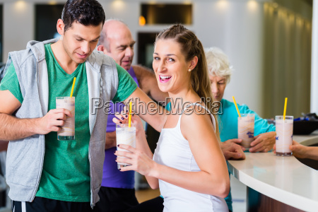 people drinking protein shakes in fitness