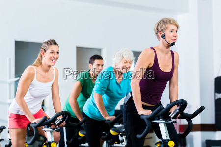 senior people in gym spinning on
