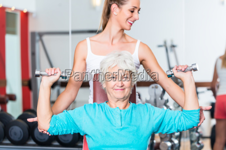 senior woman with trainer in gym