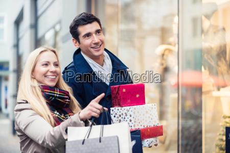 paar im schaufenster beim weihnachtseinkaufen