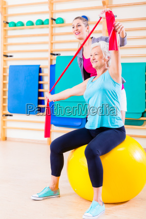 aeltere frau mit stretchband bei fitness