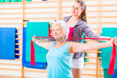 aeltere frau mit stretchband am fitness
