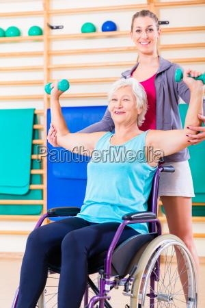 aeltere frau im rollstuhl mit physiotherapie