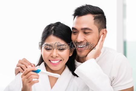 asiatisches paar mit schwangerschaftstest im bett