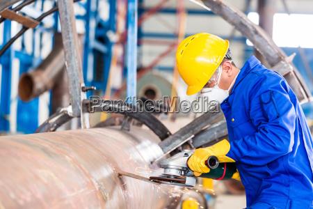 metallarbeiter im zermahlenden metall der fabrik