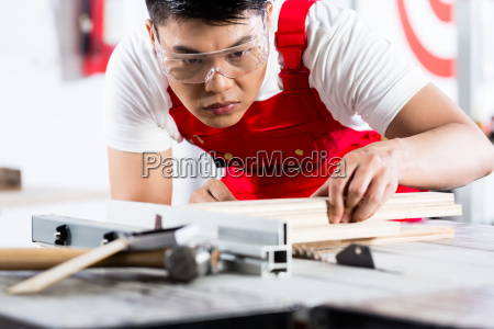 asian chinese carpenter cutting wood with