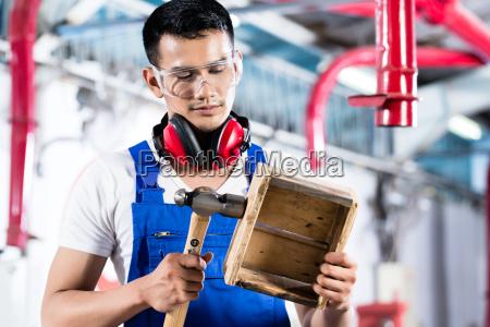asian carpenter in wood workshop working