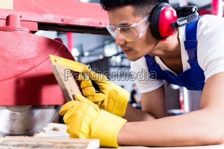 carpenter in asian workshop with circular
