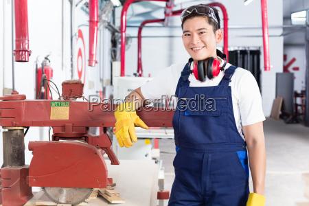 korean wood carpenter in workshop with