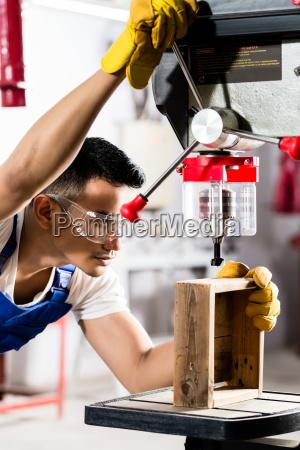 asiatische arbeiter auf bohrmaschine in der