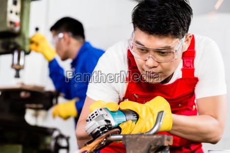 two industrial workers in asian metal