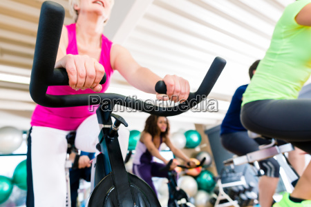 senior woman at fitness spinning on