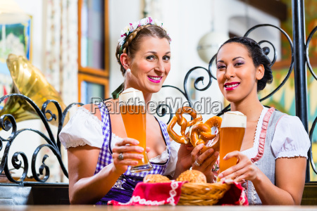 girlfriends with pretzel and beer in