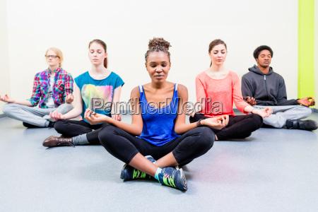 junge frauen und maenner mit yoga