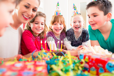 child on birthday party blowing candles