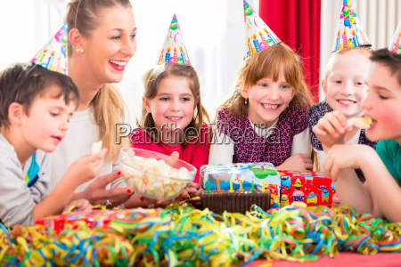 children on birthday party nibbling candies