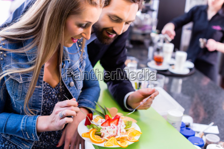 woman eating fruit sundae in ice