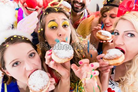 karneval party menschen essen donuts