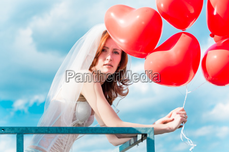 bride with red balloons on balcony
