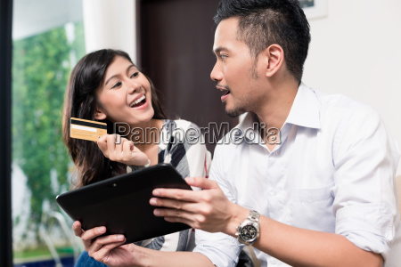 indonesian couple electronic shopping on tablet