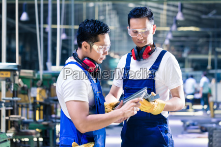 asian worker checking work piece in