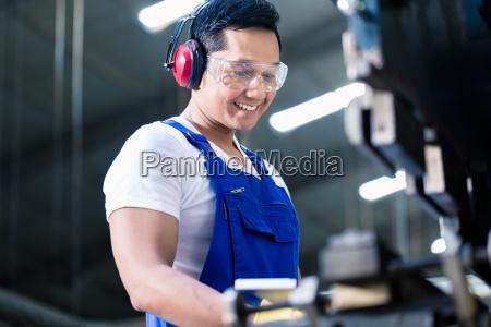 asiatischer arbeiter der metall ueberspringt in