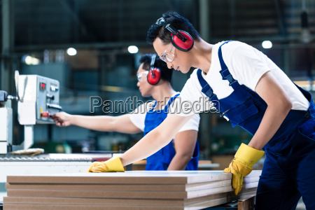 two wood workers in carpentry cutting