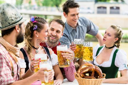 freunde im bayerischen biergarten im sommer