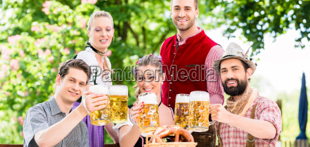 friends in bavarian beer garden drinking