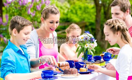 family having coffee time in garden