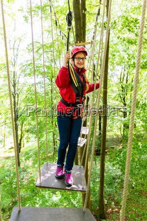 teenager maedchen klettern in hochseilgarten oder
